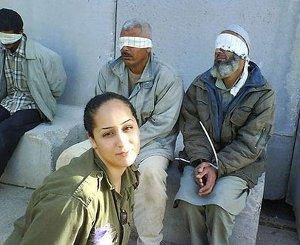Una soldado del estado terrorista de Israel se fotografía junto a prisioneros
